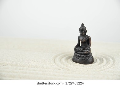 Buddha and abstract Zen drawing on white sand. Concept of harmony, balance and meditation, spa, massage, relax. Zen garden.