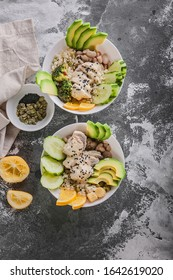 Buddha bowl with chicken meat, bulgur, white beans, quinoa, avocado, lemon and fresh cucumber. Vertical shot