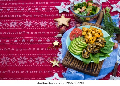 Buddha bowl for Christmas lunch, dinner. Fried tofu, avocado slices, mushrooms, tomatoes, spinach. Healthy vegetarian food. Red tablecloth. Space for text
