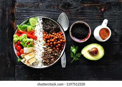 Buddha bowl. Clean and balanced healthy food concept. Rice, spicy chickpeas, black quinoa, vegetables and chicken fillet on dark wooden background, top view