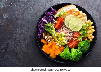 Buddha bowl dish with chicken fillet, brown rice, avocado, pepper, tomato, broccoli, red cabbage, chickpea, fresh lettuce salad, pine nuts and walnuts. Healthy balanced eating. Top view