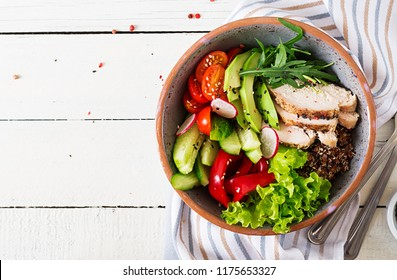 Buddha bowl dish with chicken fillet, quinoa, avocado, sweet pepper, tomato, cucumber, radish, fresh lettuce salad and sesame. Detox and healthy superfoods bowl concept. Overhead, top view, flat lay