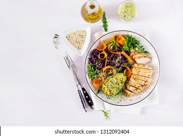 Buddha bowl dish with chicken fillet, avocado, red cabbage, carrot, fresh lettuce salad and sesame. Detox and healthy keto diet bowl concept. Overhead, top view, flat lay, copy space