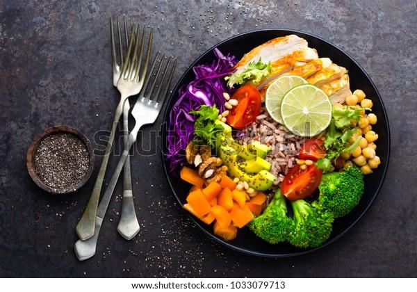 鶏のすみ肉、玄米、アボカド、ペッパー、トマト、ブロッコリー、赤キャベツ、ヒヨコ豆、新鮮なレタスサラダ、松の実、クルミの入ったブッダ・ボウル料理。健康でバランスの取れた食事。トップビュー