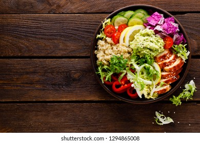 Buddha bowl dish. Healthy balanced lunch with quinoa, grilled chicken meat, lettuce salad, pepper, cucumber, tomato and avocado guacamole with lemon