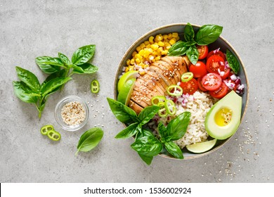 Buddha bowl with grilled chicken breast, tomato, onion, corn, avocado, fresh basil salad and rice, healthy balanced eating for lunch