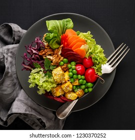 Buddha bowl,  healthy and nutritious salad with a variety of vegetables, nuts and tofu cheese,delicious and nutritious vegan meal, top view