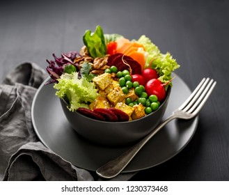 Buddha bowl,  healthy and nutritious salad with a variety of vegetables, nuts and tofu cheese,delicious and nutritious vegan meal. Healthy eating concept