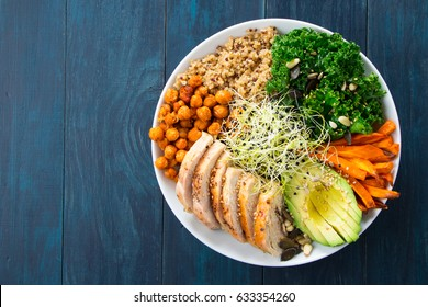 Buddha bowl with kale salad, quinoa, roasted chickpeas, grilled chicken breast, avocado, baked sweet potatoes, leek sprouted seeds, pine nuts, sesame and seeds.