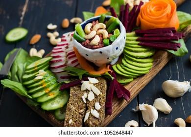 Buddha bowl on wooden board with vegetables: cucumbers, flax bread, sorrel radish, avocado, beetroot, carrot, cashew dip sauce. Top view. Raw, vegan, vegetarian food
