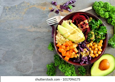 Buddha bowl with quinoa, avocado, chickpeas, vegetables on a dark background, Healthy food concept. Top view, side border with copy space.