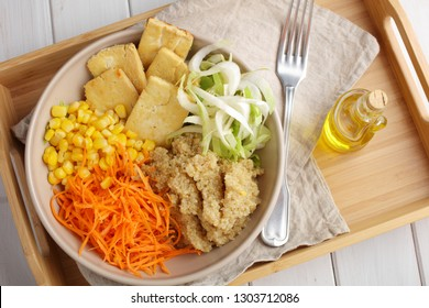 Buddha bowl with quinoa, fried tofu, chicory, carrot, corn, and olive oil