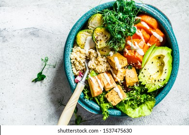 Buddha bowl with quinoa, tofu, avocado, sweet potato, brussels sprouts and tahini, copy space. Healthy vegan food concept.