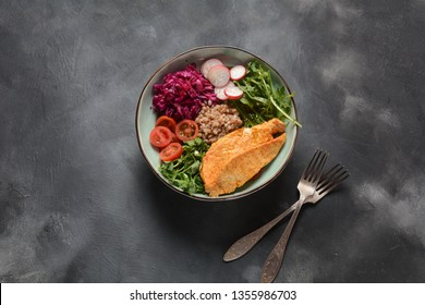 Buddha bowl with red cabbage, tomatoes, radish, arugula beet leaves, pea shoots, buckwheat, grilled chicken. Healthy food concept