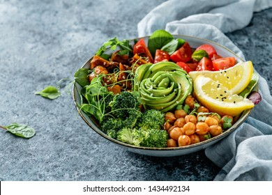 Buddha bowl salad with baked sweet potatoes, chickpeas, broccoli, tomatoes, greens, avocado, pea sprouts on light blue background with napkin. Healthy vegan food, clean eating, dieting, closeup