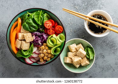Buddha bowl salad with chickpeas, sweet pepper, tomato, cucumber, red cabbage kale, fresh radish, spinach leaves and tofu cheese, healthy balanced clean eating concept, top view, flat lay