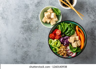 Buddha bowl salad with chickpeas, sweet pepper, tomato, cucumber, red cabbage kale, fresh radish, spinach leaves and tofu cheese, healthy balanced clean eating concept, top view, space for a text