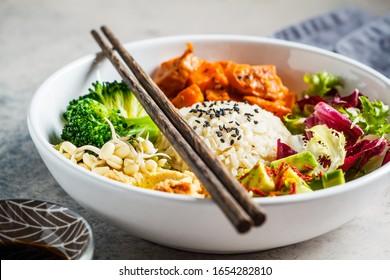 Buddha bowl. Vegan rice and vegetables salad. Macrobiotic set with rice, hummus, avocado, broccoli and sweet potato.