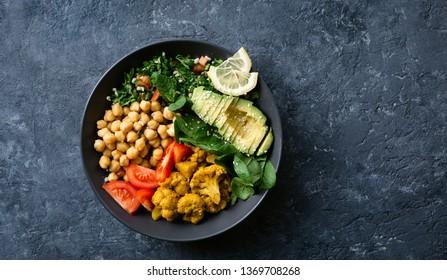 Buddha bowl. Vegetarian healthy balanced food. Aloo gobi, chickpeas, tomato, avocado, tabule salad and spinach