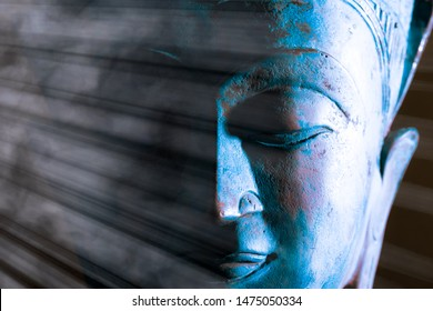 Buddha face close-up. Spiritual enlightenment. Zen Buddhism. Traditional Thai statue with ethereal light. Peaceful blue tone meditation image. Awakening the mind of self with Buddhist mindfulness.