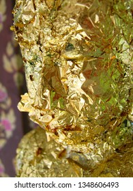 Buddha face covered in gold leaf