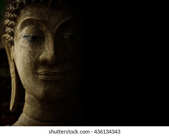 Buddha face with light and shadow on black background.