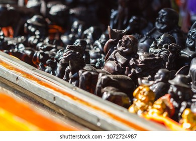 Buddha figurines and Buddhist souvenirs being sold on a boat at the floating market in Thailand
