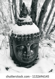 A Buddha head statue in snow