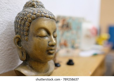 A Buddha head statue stands on a shelf near the wall in the room