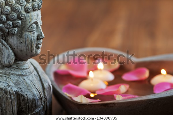 buddha head with stone heart, filled with water, rose petals and floating candles