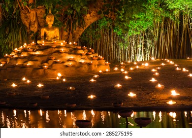 Buddha image with mediation prosture placed under Bodhi with many candles for commemorate Visakha Bucha day.