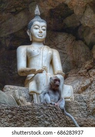 Buddha image relaxing with monkey in Thailand cave