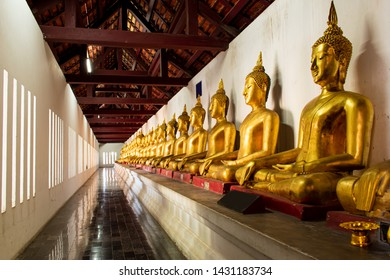 Buddha images arranged along the temple wall, Phitsanulok, Thailand.