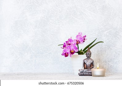 Buddha, orchid flower and burning candle as zen background