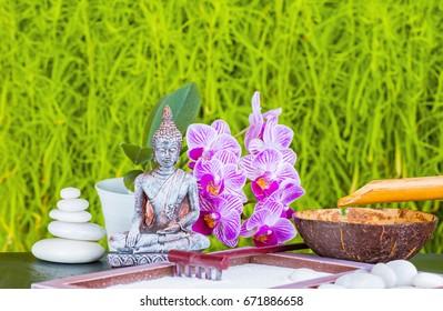 Buddha, orchid flower, candle, rake, sand and zen stones as zen garden background