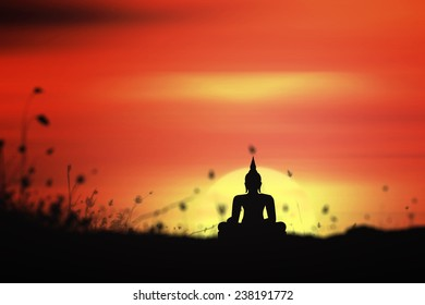 Buddha Purnima and 	 waisak day concept: Silhouette buddha statues on blurred meadow sunset background
