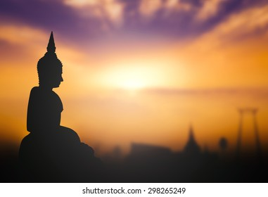 Buddha Purnima Day concept: Silhouette Buddha with blurred tourist attraction on golden sunset background.