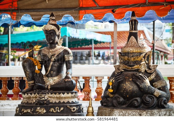Buddha and Rahu sculptures at Buddhist shrine in Thailand. Hindu deities black and golden sitting statues