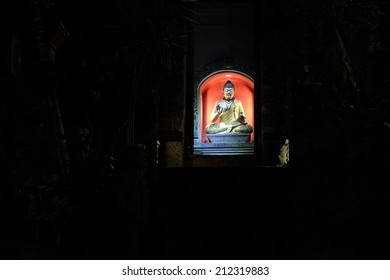 A buddha shrine on the side of the road at night