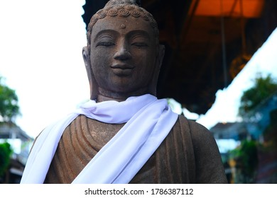 The Buddha smiles at the camera. A white scarf flutters in the wind.