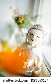 Buddha - soft toy sits on a window and looks into the camera isolated on a white background with flowers