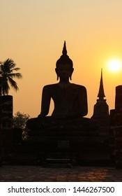 Buddha statue against sunset silhouette, Wat Maha That, Sukhothai, Thailand
