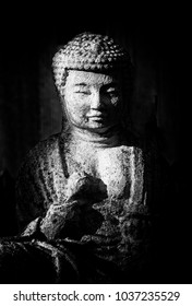Buddha statue in black and white against a black background