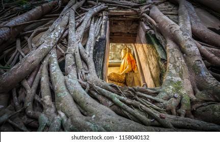 Buddha statue church old brick wall and tree root in Wat Bang Kung Samut Sakhon Thailand