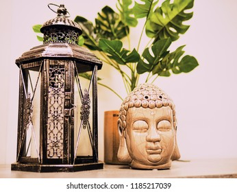 Buddha statue in modern home, Home decoration. Candle Lighter and Buddha Head statue and Monstera's Leaves. Holidays decoration.