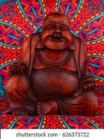 Buddha statue on a colorful background / featuring a wooden statue of  cheerful wise Buddha on colorful Oriental artistic pattern background