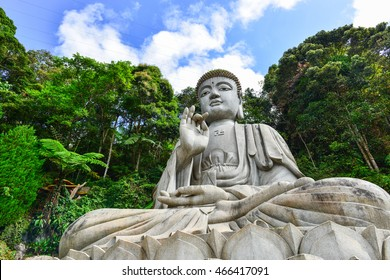 A Buddha statue overlooks a valley through the trees and the mist at the Chin Swee Caves in Malaysia in the Genting Highlands.