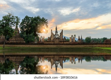 Buddha statue and pagoda Wat Mahathat temple with reflection during sun set, Sukhothai Historical Park, Thailand