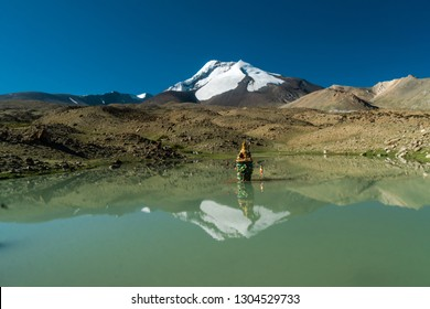 Buddha statue in picturesque reflecting lake in Himalayas on sunny summer day. Ladakh, India.