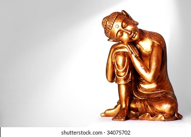 A Buddha statue resting, in front of a gray background with a spotlight.